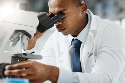 Male doctor looking into microscope.