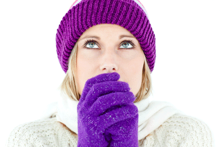 Woman blowing on hands to keep warm