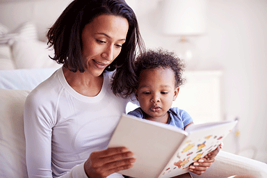 Close up of mixed race young adult mother sitting in an armchair reading a book with her baby son