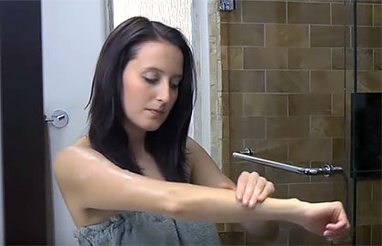 Woman applying self-tanner in shower