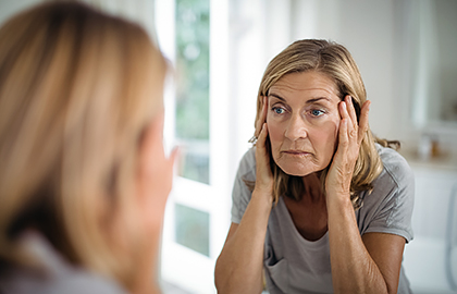 Woman looking at sagging skin in mirror