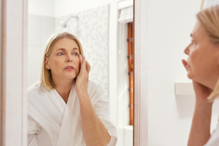 Image of a mature woman looking at herself in the bathroom mirror