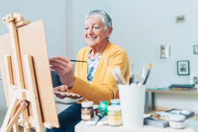 older woman painting in studio