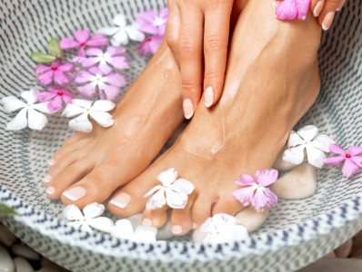 woman's feet in water bowl with flowers