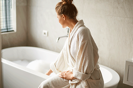 Self-care treatment concept. Side portrait of young woman sitting on tub and touching water before taking bath.