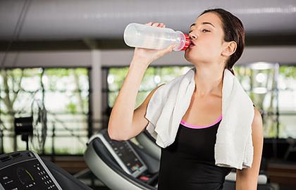 Woman at gym drinking water