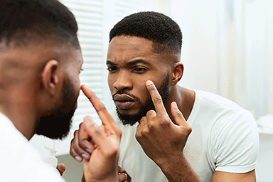 Young African American man touching face, examining quality skin, looking at mirror in bathroom