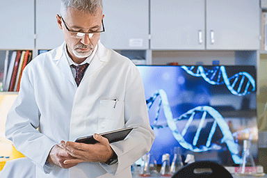 Male genetic research scientist working with a tablet in a laboratory with a computer monitor in the background showing DNA structure.