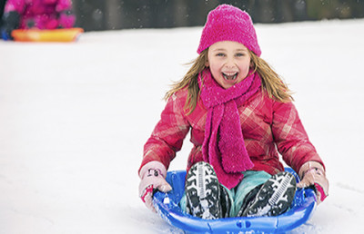 Girl on sled: Dry air, cold temperatures, and indoor heating can irritate your child's skin, causing eczema to flare.