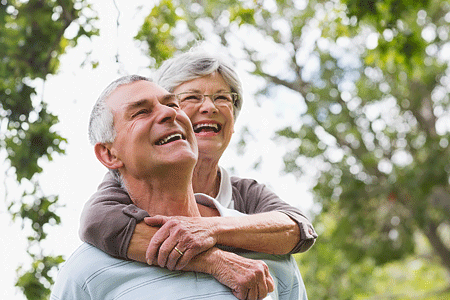 Cheerful senior woman embracing senior man from behind at the park