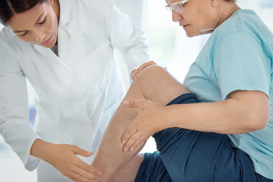 Side view of female dermatologist examining legs and calves of a senior female patient
