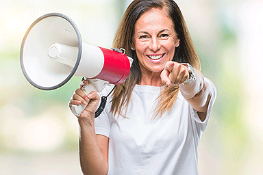 Middle age woman holding a megaphone with finger pointing to you