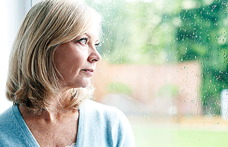 Worried woman looking out window during a rain shower