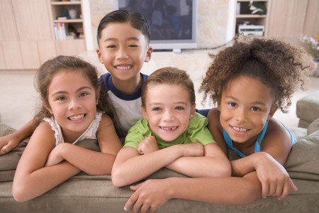 4 smiling children leaning on the back of a couch
