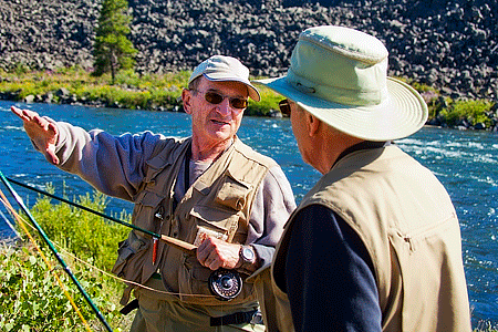 Two fisherman wearing hats, sunglasses, long sleeves, and pants talking outdoors