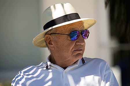 Older man relaxing outdoors in the shade, wearing a hat and sunglasses