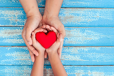 Red heart in child kid and mother hands on old blue wooden table background