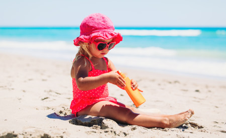 Young girl on the beach playing in sand wearing protection from the sun