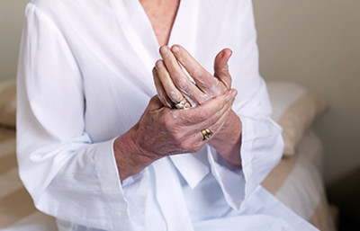 woman putting lotion on aging hands
