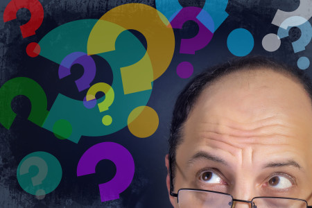 Man looking at question marks expressing confusion