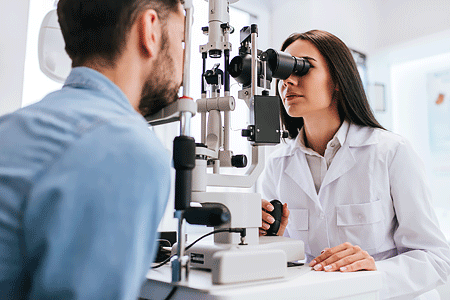 Female doctor ophthalmologist checking the eye vision of a young man.
