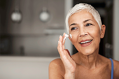 Senior woman applying anti-aging cream to her face.