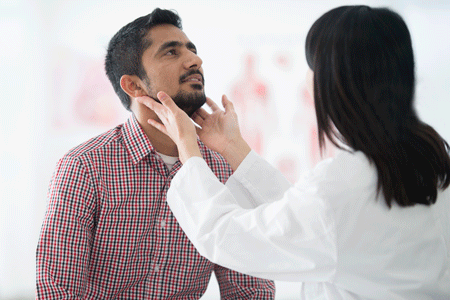 Close-up of man getting lymph nodes in his neck checked by a doctor