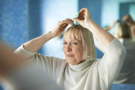 older woman applying ointment to scalp