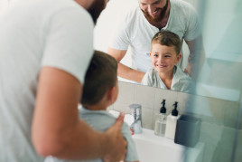 father and son looking in mirror