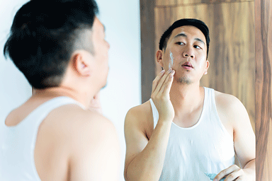 Asian male in white shirt using a skincare cream for face in front of mirror in bathroom