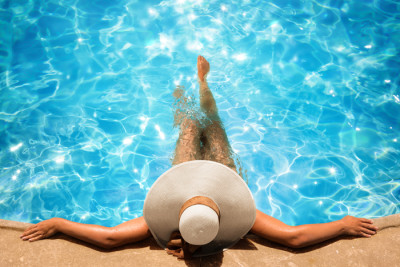 Person in a pool with a sun-hat