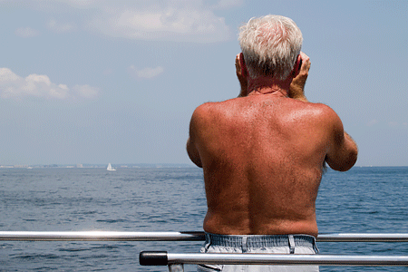 Suntanned back of elderly man that is peering out over blue water. Expresses concepts of sun exposure.