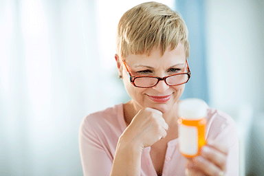 Mature woman with hand on chin reading label on prescription medicine bottle