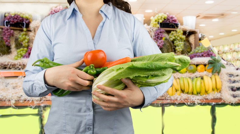 woman in grocery produce section holding vegetables