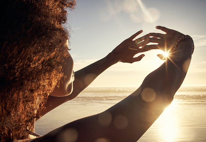 Young woman blocking the sun with her hands