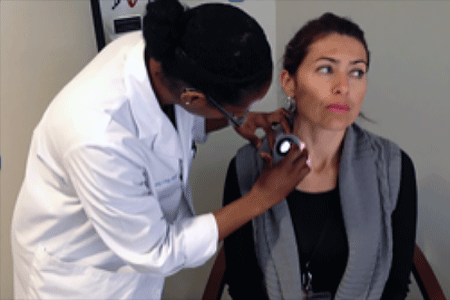 Dermatologist performing skin cancer screening on a woman