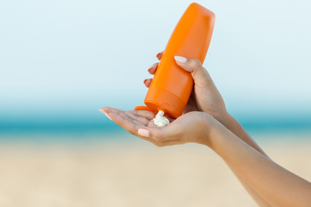 Sunscreen being squeezed out of a bottle