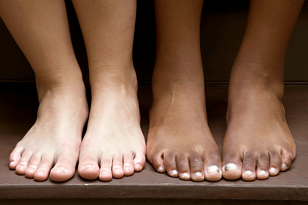 Close-up of bare feet for a Caucasian person and an African American person