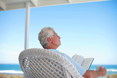 Senior man reading book on patio by the beach