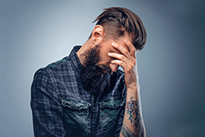 Stressed man with tattoo on his arm