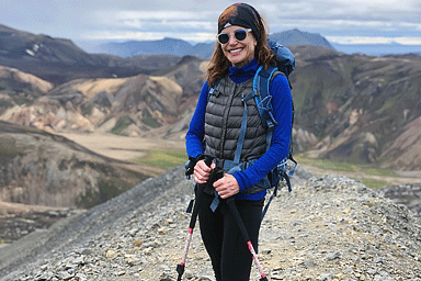 woman with hiking poles on a mountain trail