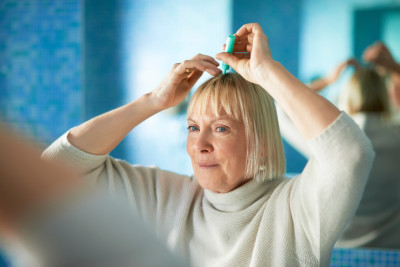 woman applying medicine to scalp