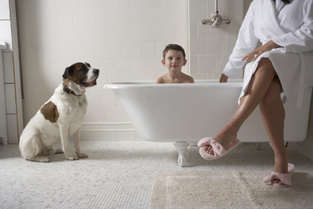 Mother sitting on side of tub with son in bath tub and with dog