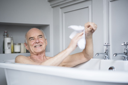 Senior man in bath washing himself