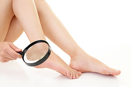 Woman doing skin exam using magnifying glass on her ankle