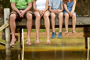 Family sitting on pier wearing flip-flops