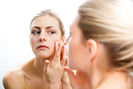 Woman examining skin on her face in the mirror