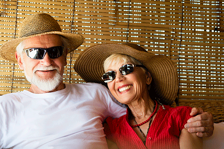 Cheerful senior couple wearing straw hats, woman has blond short hair and man has gray hair and beard
