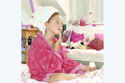 Girl with hair in towel sitting on bed applying moisturiser