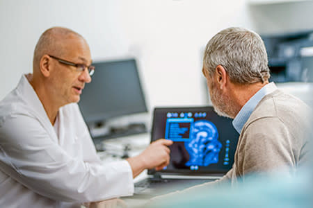 Male doctor reviewing brain scans on computer with male patient